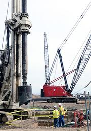 Workers set up equipment to build the interchange that will serve Delta Shores.