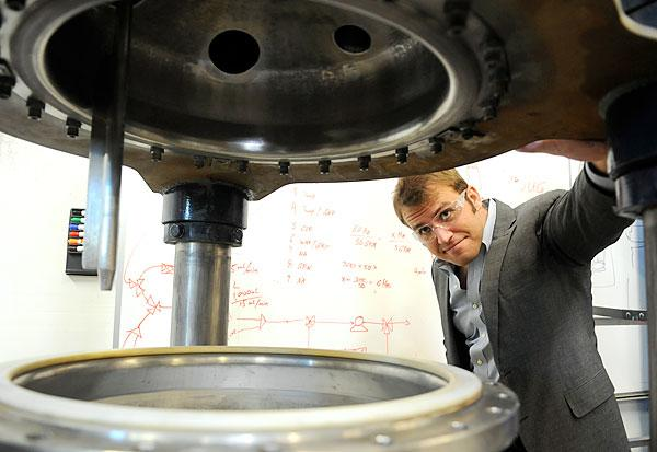 Micromidas CEO John Bissell looks into a reactor that digests cellulose. Micromidas plans to convert cellulosic waste material into paraxylene, which is used to make plastics.