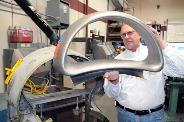 Snowline Engineering executive sales manager Lee Block holds a part for the Lockheed P3-Orion. Snowline has created a niche making replacement parts for old airplanes.