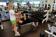 Verizon fitness trainer Jessica Byers helps employee Michele Lyon with a bench press at the company's gym.