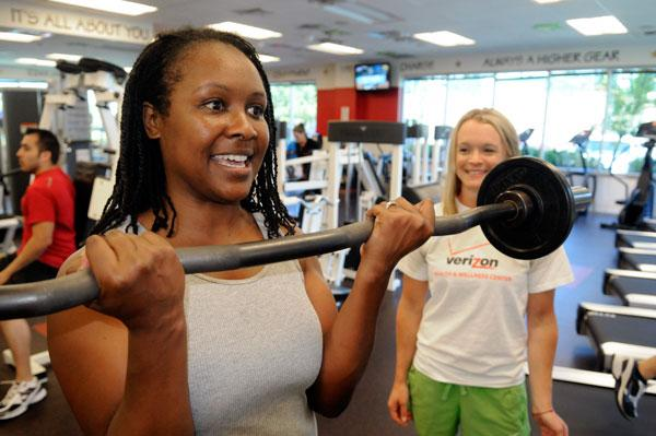 Verizon employee Erica Casebeer does bicep curls at the company's gym under the watchful eye of on-site fitness coach Jessica Byers.