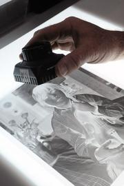 Jeff Cox looks at a negative on a light table. His lab is one of the few that processes film by hand.