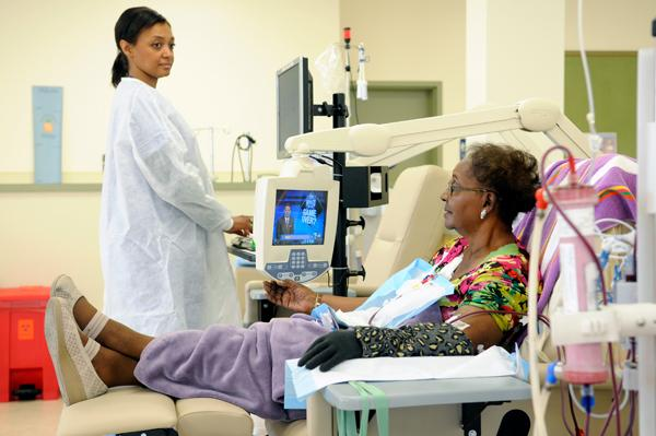 Clinical coordinator Travita Amos works with patient Dolores Dixon at Calvine Dialysis.