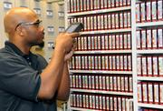 Darriel Perry, supervisor of DataSafe's Sacramento operations, uses a bar code scanner to check magnetic tapes on file.