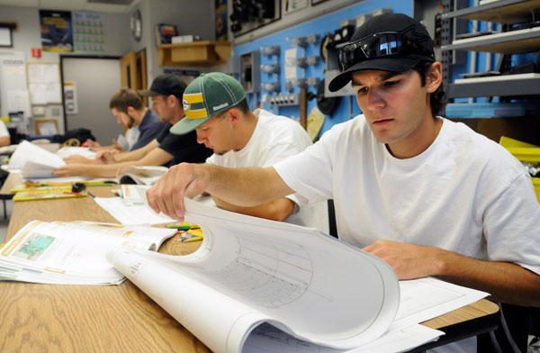 Jeff Gallegos, right, and others in the third year of the apprenticeship program at International Brotherhood of Electrical Workers Local 340 training center, use blueprints for their research.