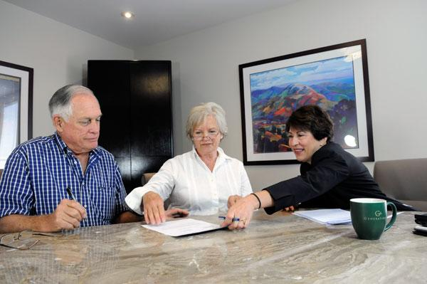 Estate-planning attorney Trudy Nearn, right, says problems arise when a trustee acts on his or her own interpretation of the trust instructions. At left, she assists clients Marshall and Nancy Kraus.