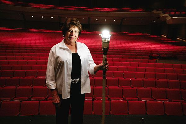 "Convention Center manager Judy Goldbar, holding  the theater's ""ghost"" light, says part of the renovation funds comes from a $3 fee tacked onto all ticket sales."