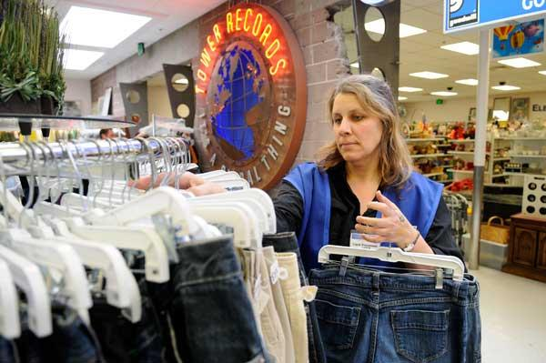Karen Barner-Vorse restocks the racks at the Goodwill store in the former Tower Records location at Watt and ElCamino avenues.