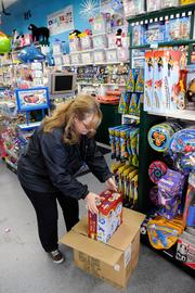 Learning Express store manager and buyer Colleen Hendon stocks the shelves.