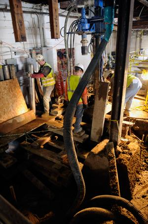 Workers are drilling 31 micro piles as part of the seismic retrofit for the Hotel Berry.