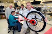 Wijit's CEO Harry Laswell shows the Wijit wheelchair device being manufactured by Pride Industries. In the back­ground, Wijit's John Rhea, left, and founder Brian Watwood watch as Pride manufacturing engineer James Milbourne works.