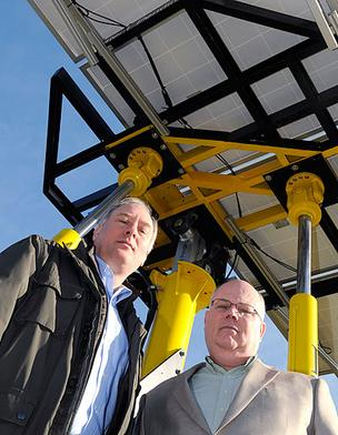 Inspired Solar Technologies chief commercial officer Jurgen Krehnke, left, and CEO Ken Ooosting, stand next to their prototype solar tracker at William Jessup University in Rocklin. The prototype holds four solar panels. A larger tracker under constructio