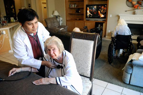 Senior Care by RNs founder Ron Ordona checks resident Lorraine Shodeen at the company's board-and-care facilty in Lincoln.