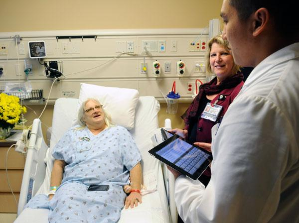 Nurses Terri Owensby and Huy Tran at Kaiser Permanente South Sacramento Medical Center, a pioneer in the use of electronic medical records, bring iPads to the bedside to track information about patient Laurie Norling.