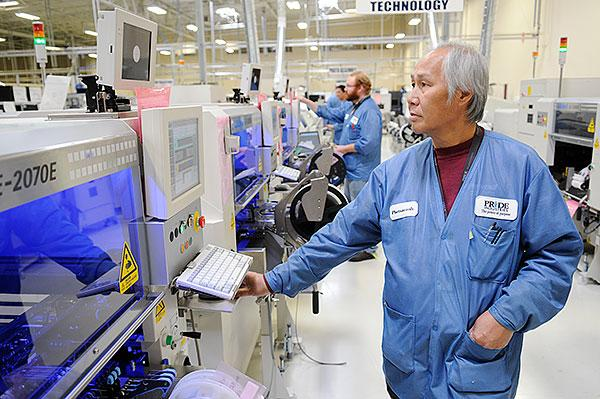 Phetsavanh Phommachith monitors a production line at Pride Industries that automates the placement of thousands of tiny components onto printed circuit boards. The boards then are assembled into electronic devices for customers such as SynapSense.