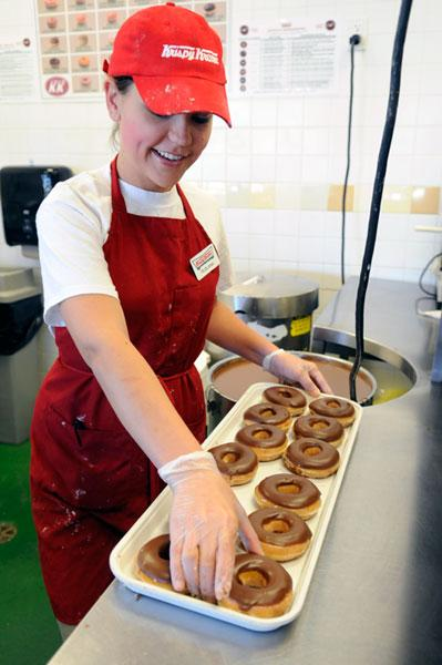 Ruslana Pyavka glazes doughnuts at Roseville's new Krispy Kreme. The local franchisee wants to add five stores in the region.