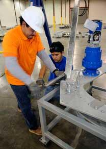 Hernan Ruiz, left, and Raul Santacruz assemble a solar tracker at OPDE in 2010. The company recently filed for bankruptcy.