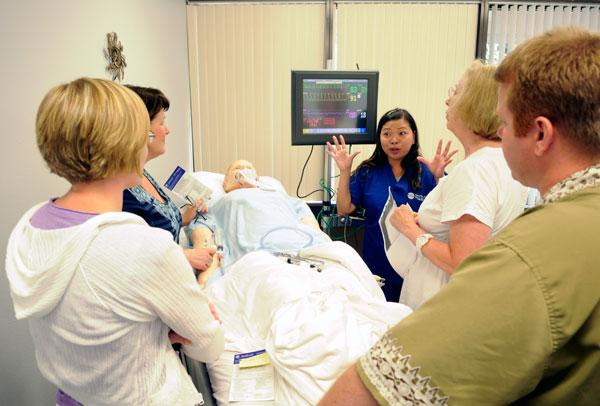 Nurses from Sutter Auburn Faith Hospital learn about sepsis symptoms from a dummy patient.