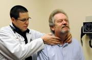 Dr. Gregory Spears examines patient Dennis Owen.  Osteopathic physicians at times use manipulation to treat patients.
