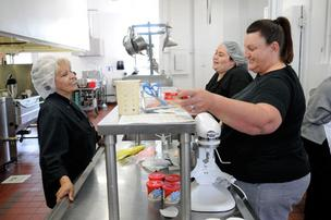 Mary Scott, Nicole Brock and Angela Pyle, from left, prepare icing for cupcakes at Plates Cafe.