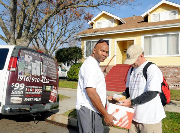 Koid Starks, left, owner of Take 1 Marketing Distribution Services, gives advertising materials to distributor Dave Richey.
