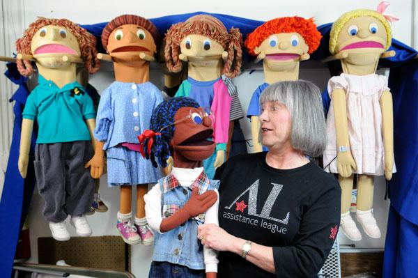 Charlotte Stott, president of the Assistance League of Sacramento, practices with puppets they use in shows to help students learn about bullying or how to eat healthy foods.