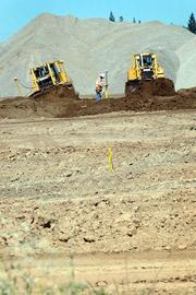 Workers are moving mountains of dirt at the Township 9 development north of downtown Sacramento near the American River.