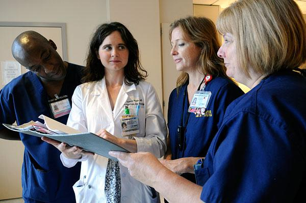 Dr. Soames Boyle, in lab coat, consults with registered nurses, from left, Darrell Desmond, Rachelle Dyer and Lauri Brunton at the UC Davis Medical Center.