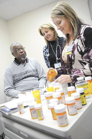 UC Davis Medical Group registered nurse Sharon Myers, center, and pharmacist Patricia Poole review the 19 medications that patient Mack Stafford must take every day.