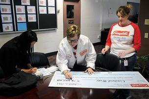Campbell Soup employees put the finishing touches on a check they were presenting Friday to the United Way. From left are United Way's Cherie Parsons, and Carol Ponce and Stephanie Mendenhall of Campbell Soup.