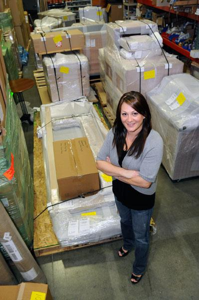 Director of business development Amber Vance stands in Wells Construction Inc.'s packed warehouse. When the company looked for a location for its satellite office, storage space was a consideration.