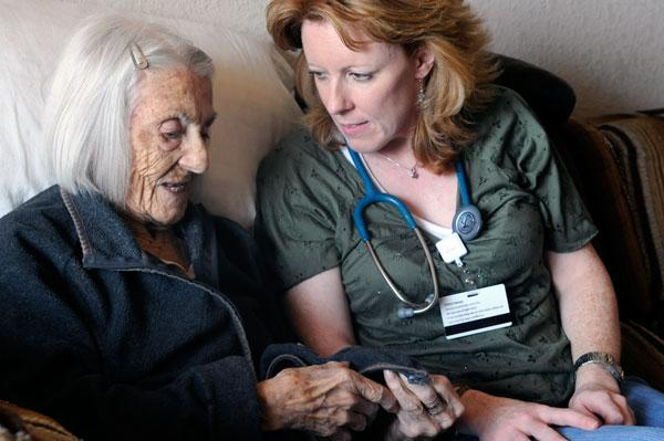 Registered nurse Kim Smith, right, checks in with hospice patient Ida May Hawkins, 98.