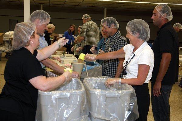 Aerojet volunteers package 11,880 meals for starving children in Haiti.