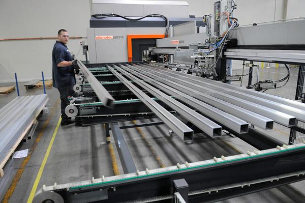 Daniel Ramirez loads extrusions for solar panels onto a machine at Mounting Systems Inc. in West Sacramento. The 30-employee company expects a 50 percent increase in revenue next year.
