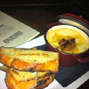 The pot of bubbly swiss cheese, roasted garlic and sweet onion is served with a side of grilled bread.