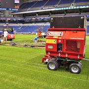 Workers prepare a portion of the 133,000 square feet of AstroTurf installed in the Alamodome for Big League Weekend.