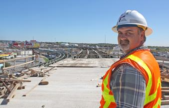 A file photo of a worker standing on the elevated bypass at Bandera and Loop 410. The Texas Department of Transportation is floating a proposal to have major cities pick up the cost to maintain certain highways.