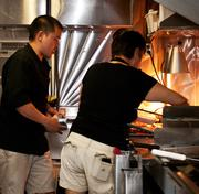 Kitchen Fusionz employees are preparing the food truck's mix of Asian fusion-theme dishes.