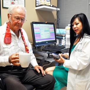 Above: Patient Charles Rudolph holds a mug while Dr. Vikki Alvarez adjusts the electronic stimulation that controls his severe essential tremors. Rudolph, 75, travels three hours to see Alvarez because his tremors improve by 75 percent with the deep brain stimulation.