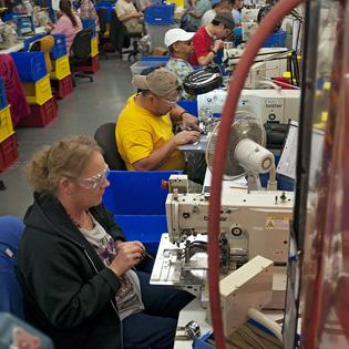 Judy Thomas [foreground] and other workers at the San Antonio Lighthouse for the Blind are assembling chin straps for a military contract at the company's headquarters on the city's South Side.