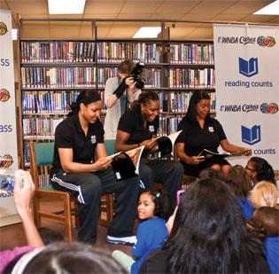 (L-R) Maya Moore and Rebekkah Brunson of the Western Conference All-Stars and WNBA President Laurel Richie read to kids gathered during the BBVA Compass Reading Counts initiative at the Keith A. Campbell Memorial Library at Fort Sam.