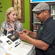 Heartland Payment Systems's Sherry Willis consults with Pedro Cabrera, the co-owner of Los Jalapeños restaurant, as he uses Heartland's mobile payment system.
