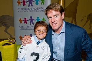 Eight-year-old Children's Hospital Oakland patient Marlon Orellana-Enriquez and Oakland Raiders quarterback Carson Palmer.