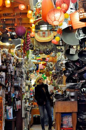 A tourist walks through one of the many gift shops on Grant Street, Chinatown's main drag. Stores just like this sit side-by-side on the street and are packet with knick-knacks and trinkets.
