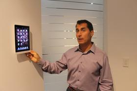 Randy Stearns, CEO of Via International, with a removable, wall-mounted iPad used to control home tech systems ranging from stereos to windows.
