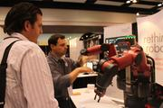"""Brian Benoit, a product manager at Boston's Rethink Robotics, shows off the pioneering """"Baxter"""" robotic arms, which can easily be trained to do repetitive tasks safely around humans. Asking questions was Jake Beahan of ZBE, a Santa Barbara manufacturer of digital image printing equipment."""