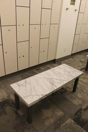 Marble salvaged from the old building has been used to make seating in the shower area next to the bike storage rooms.