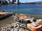 Yellow barriers were placed in the lake to control the spread of demolition debris.