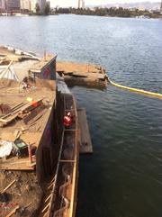 Workers preparing the cofferdam along one side of the channel before the bridge was placed across.