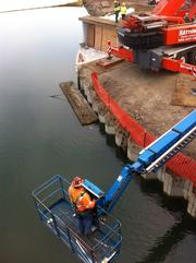 A worker maneuvered a boom lift over the water before the bridge was lifted.